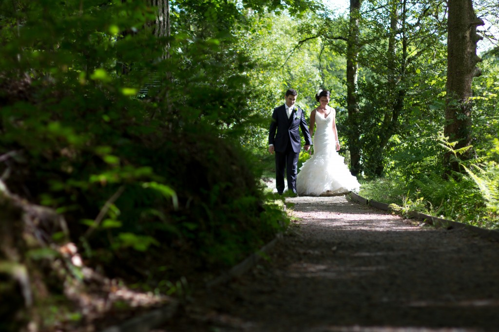 Bride and Groom Walking Through Forest in Cumbria