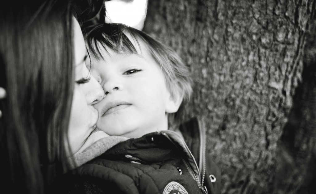 A mother tenderly kisses her son on the face. Lancashire Family Portrait Photographer