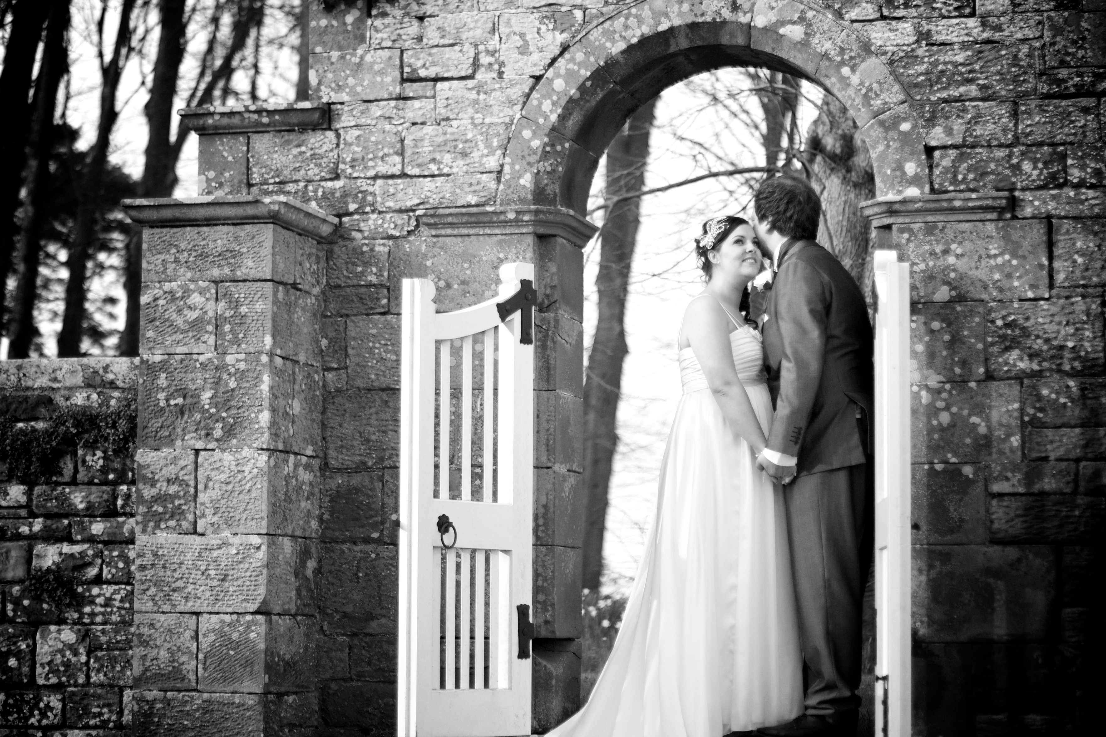 Cumbria Embracing In A Gateway The Gardens Of Dalston Hall Laughing Bride And Groom Wedding Photography