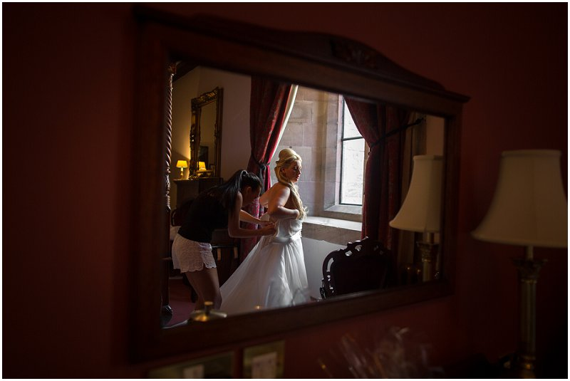 Bride getting into wedding Dress | Peckforton Castle Wedding Photography Karli Harrison Photographer