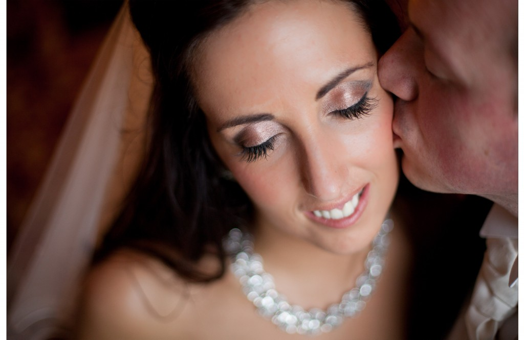 Close up of groom tenderly kissing his bride on the cheek at West Tower. Lancashire Wedding Photography