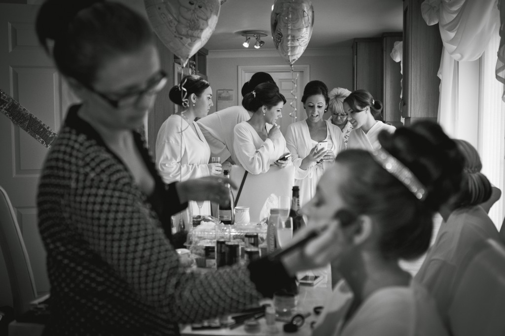 Bridesmaids share a secret text during bridal preparations. Beautiful Wedding Photography Liverpool