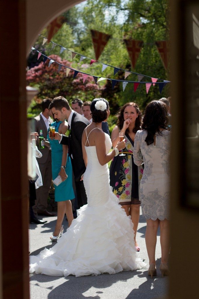 A bride celebrating outside with her guests in the glorious sunshine in Cumbria. Stunning location for wedding photography