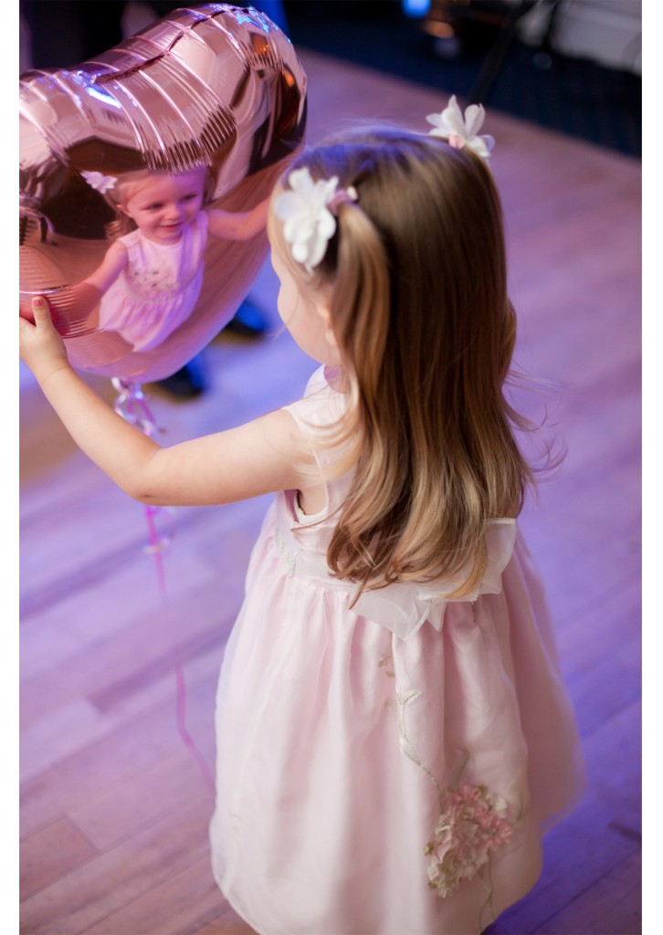 A little girl looks at her reflection in a balloon during a wedding reception