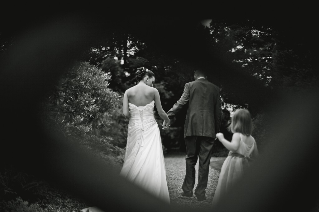 Wedding Photojournalism, bride and groom take a walk while photographer shoots through the back of a bench
