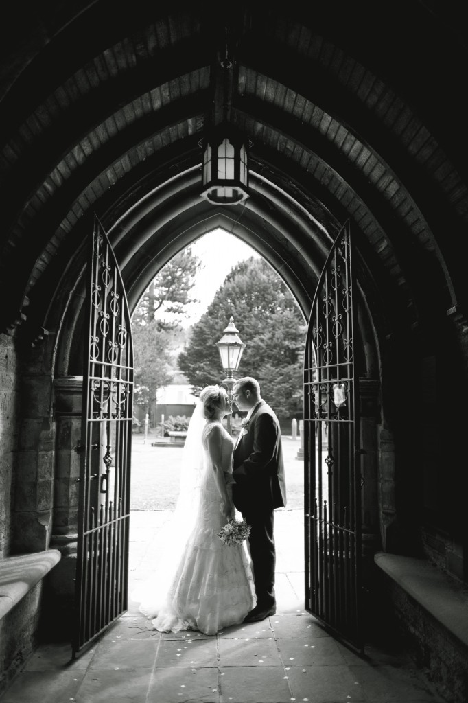 Bride and groom embrace in an archway of the church in Blackburn, Lancashire