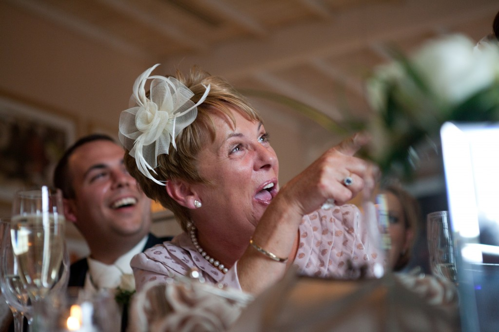 Mother of the groom laughing and pointing to best man during speeches