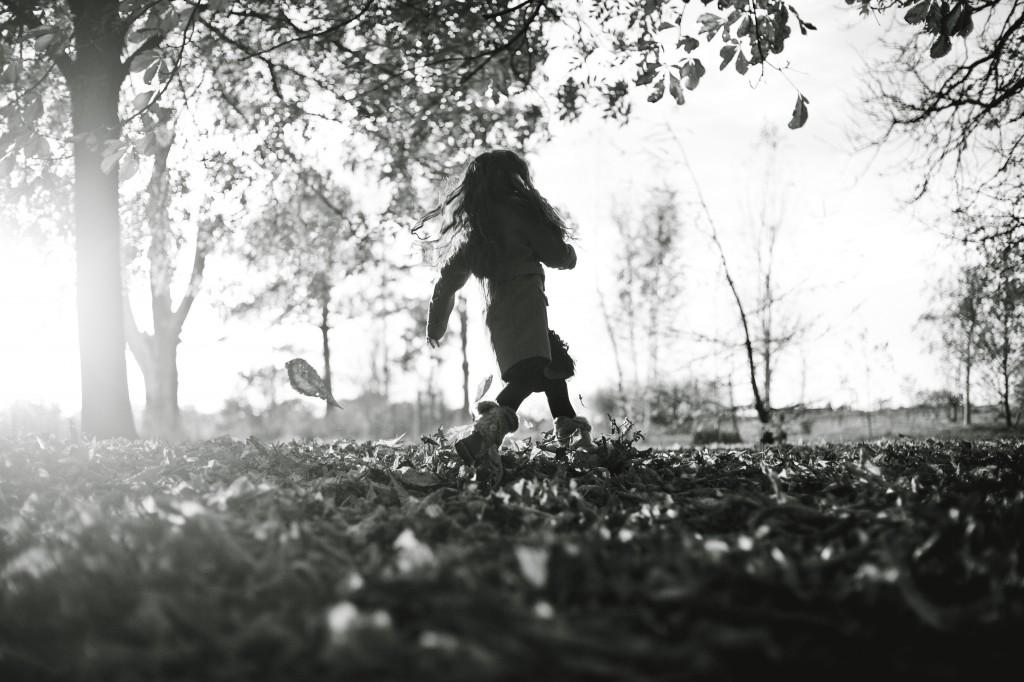 A girl running through autumn leaves in Ashton Park, Preston. Lifestyle Family Portraits