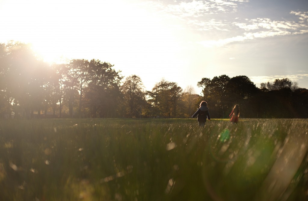 Running in the sun, two siblings charge across a field in Ashton Park, Preston