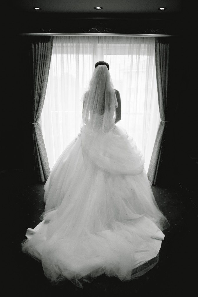 Brides Stands in Window of Suites Hotel Bridal Suite