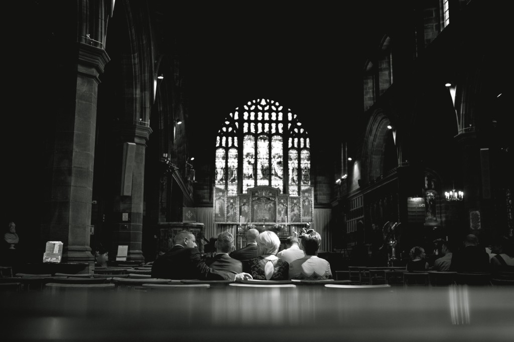 A beam of sunlight falls on wedding guests as they wait in the church for the bride. Wedding Photography Lancashire