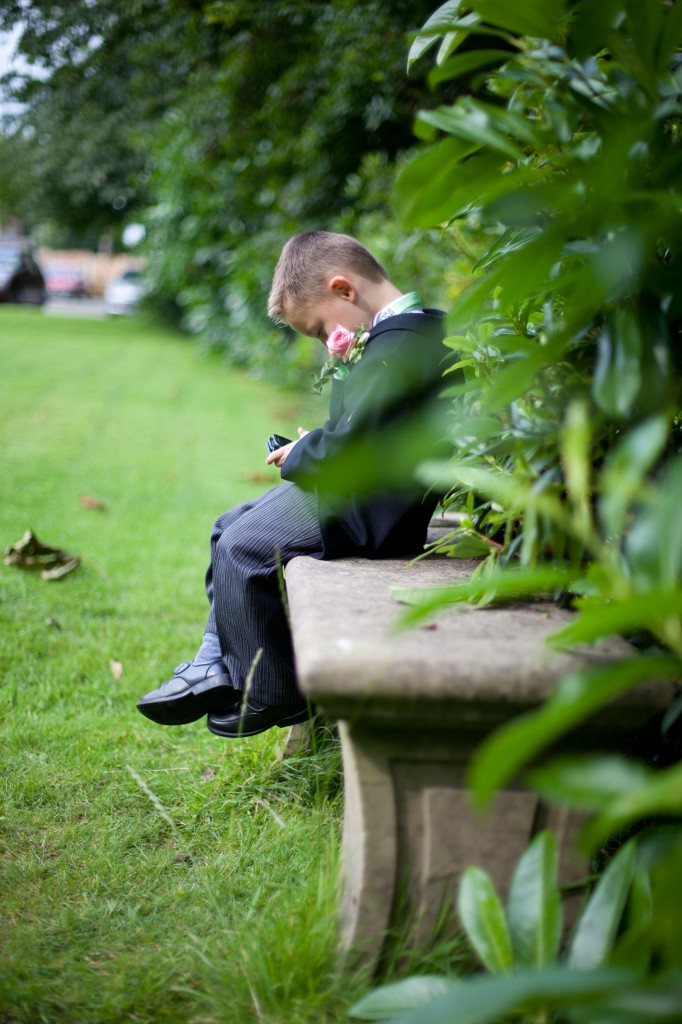 Ashfield House Hotel, the pageboy sits and plays on his DS. Lancashire Wedding Photographer