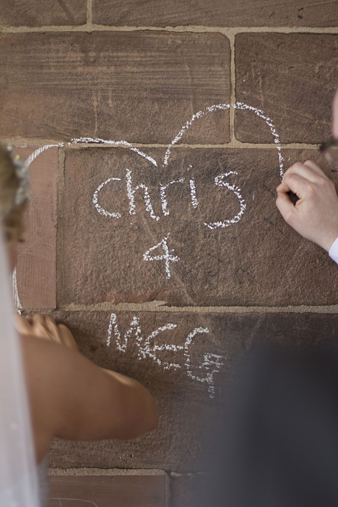 Love heart - a couple write their names on a wall in chalk