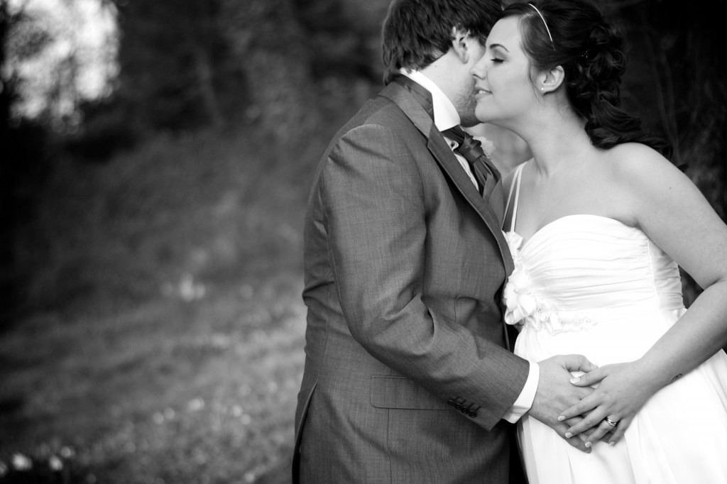 A bride and groom embrace each other, and their unborn child