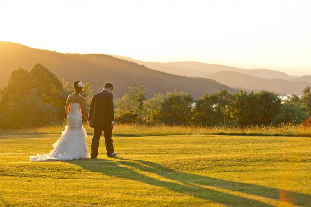 A bride and groom stroll across a field in Cumbria, near Lake Windermere