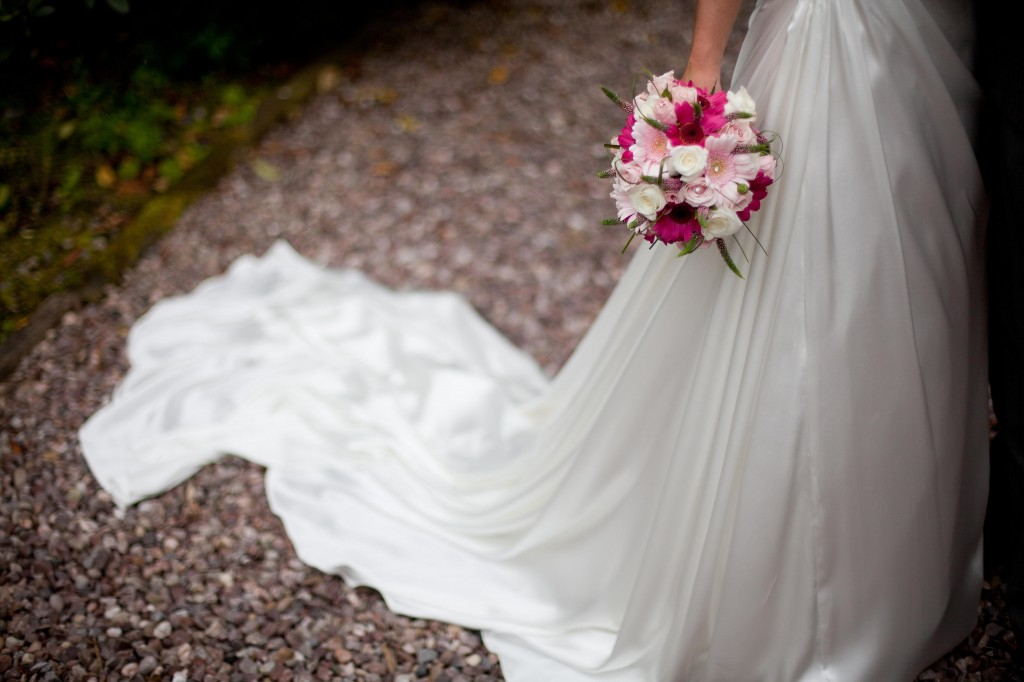 A creative shot of a bride and her flowers, and her dress from the waist down