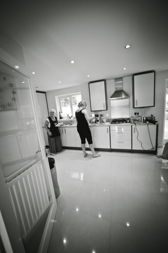 Documentary Wedding Photography, a shot of a bridesmaid getting some food in the kitchen
