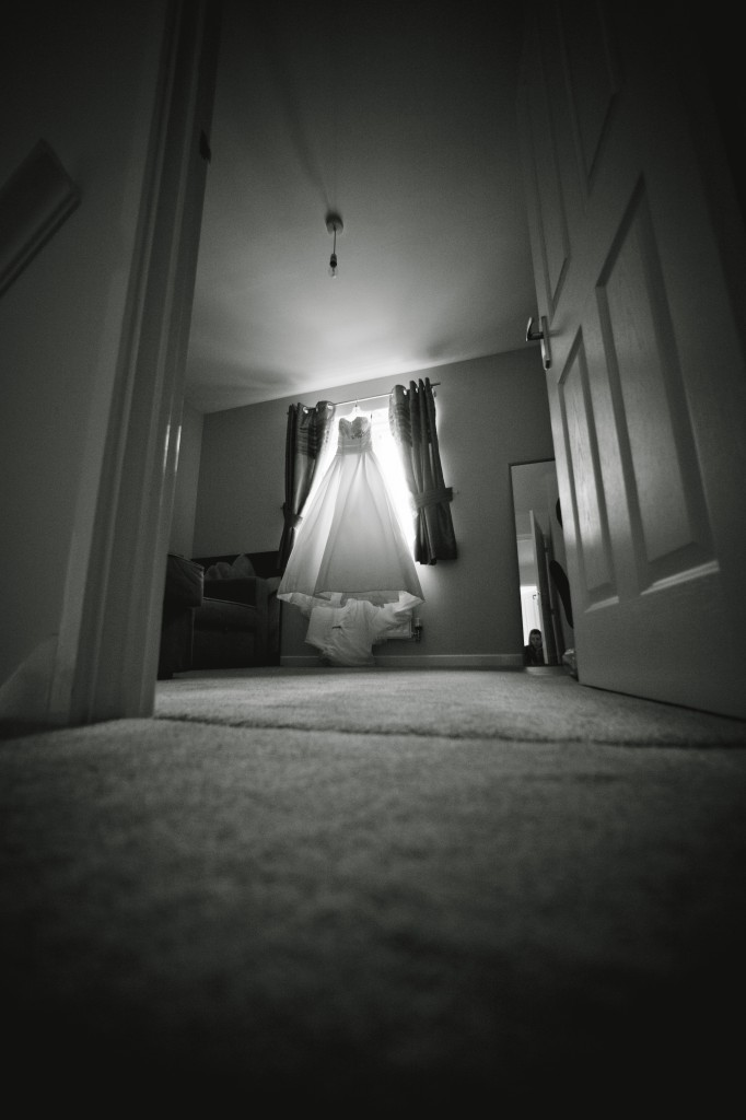 The bride's dress hanging up in a window, taken with a wide angle lens to create drama