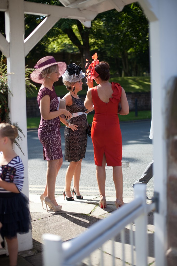 Three lady guests await the arrival of the bride