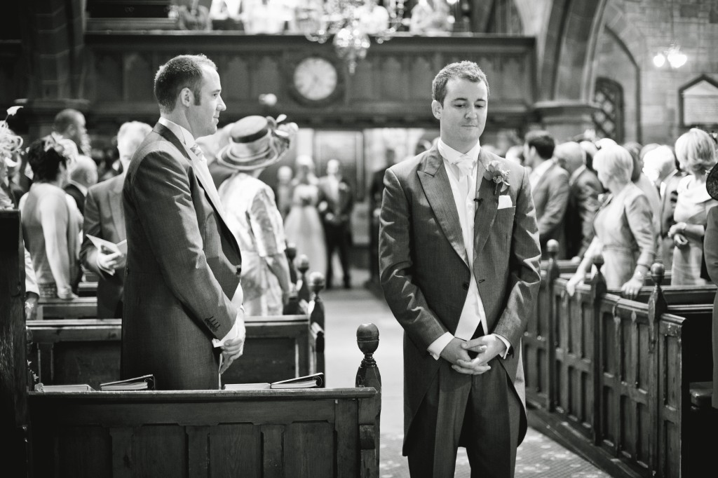 Groom waiting at the front of the church for the bride to arrive. Beautiful documentary wedding photography