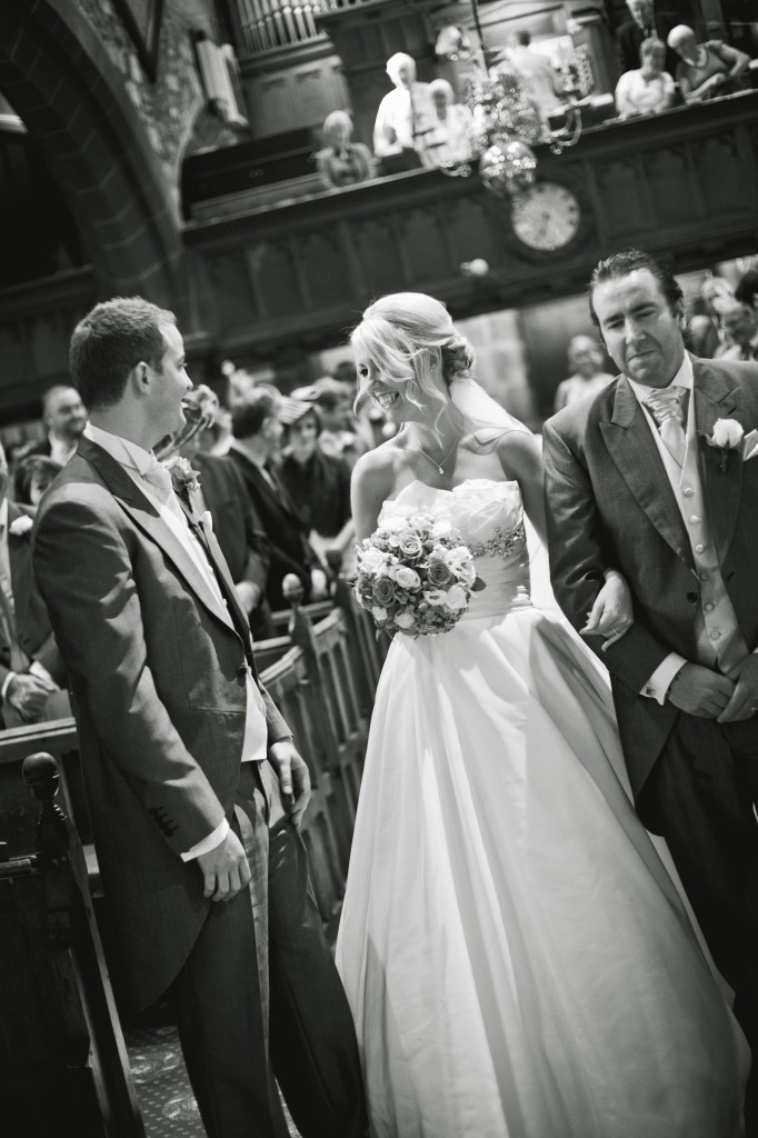 The bride greets her groom at the front of the church