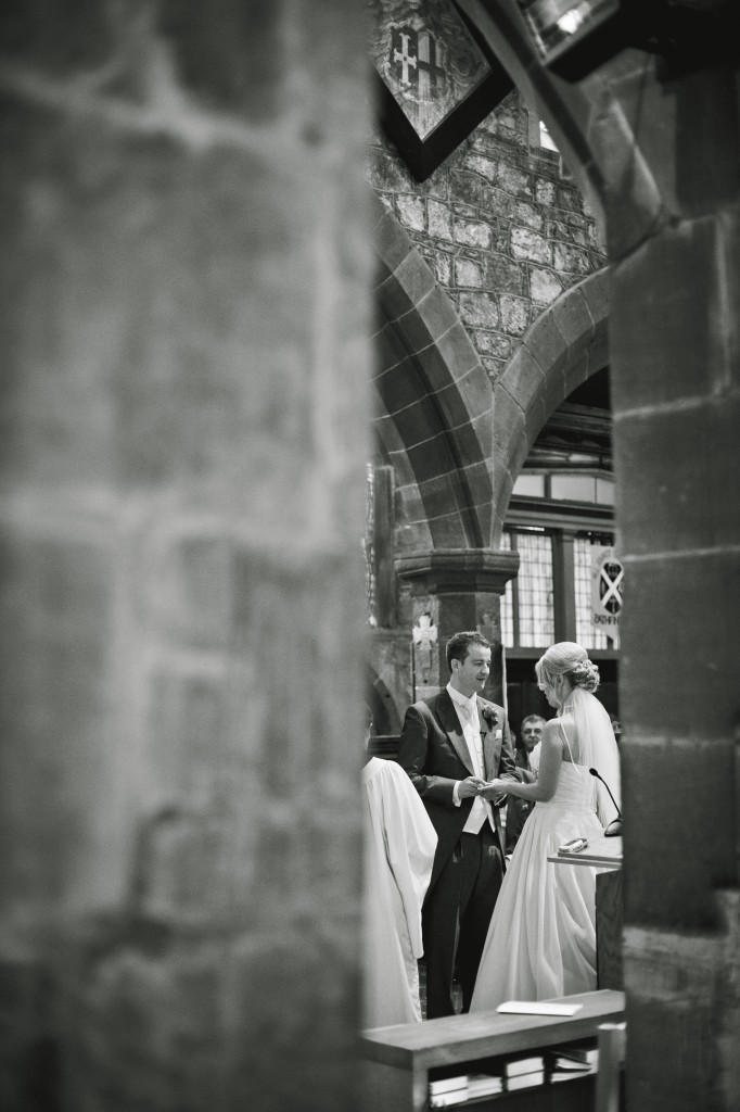 Peering through the columns of the church, photojournalism wedding photography