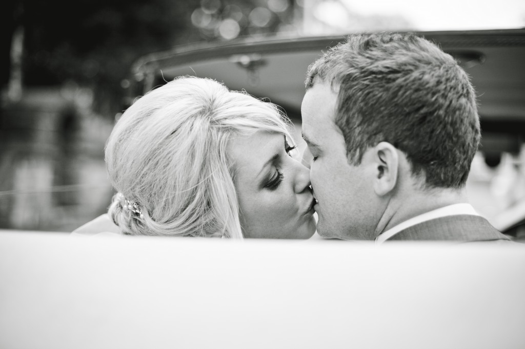 Sharing a kiss in the wedding car, a bride and groom share a tender moment perfect for wedding photography