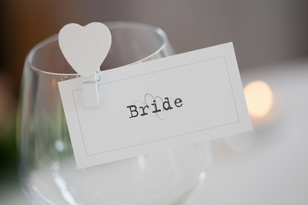 Bride place card hanging from her wine glass. Detailed wedding photography