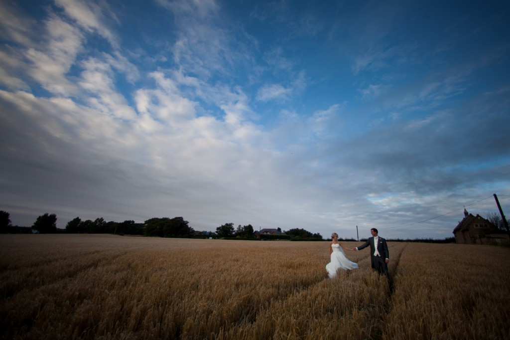 Walking through a field for their wedding photography, Lancashire