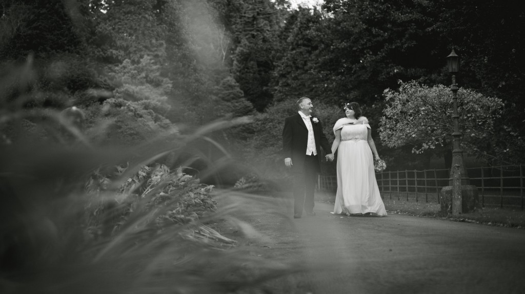 Bride and groom walking hand in hand along a pathway, Lancaster, Lancashire
