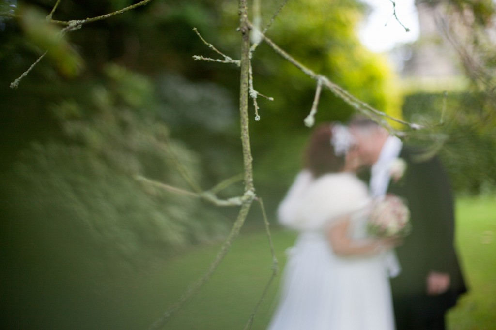 Creative photograph of tree with bride and groom out of focus