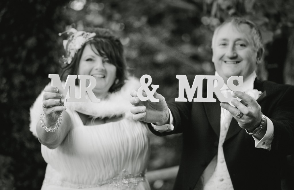 Mr & Mrs Sign being held up for creative wedding photography