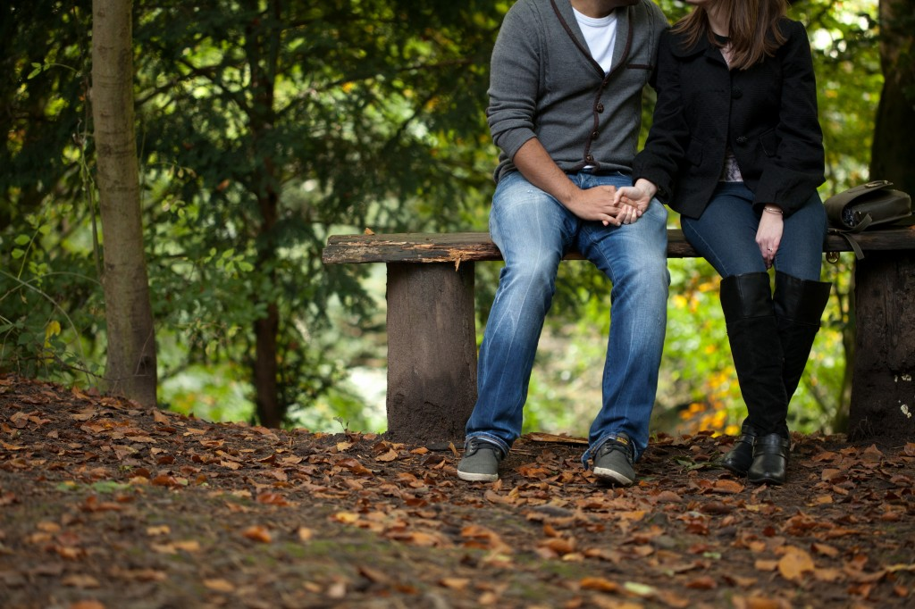 Couple sitting hand in hand in a forest, pre wedding shoot Lancashire