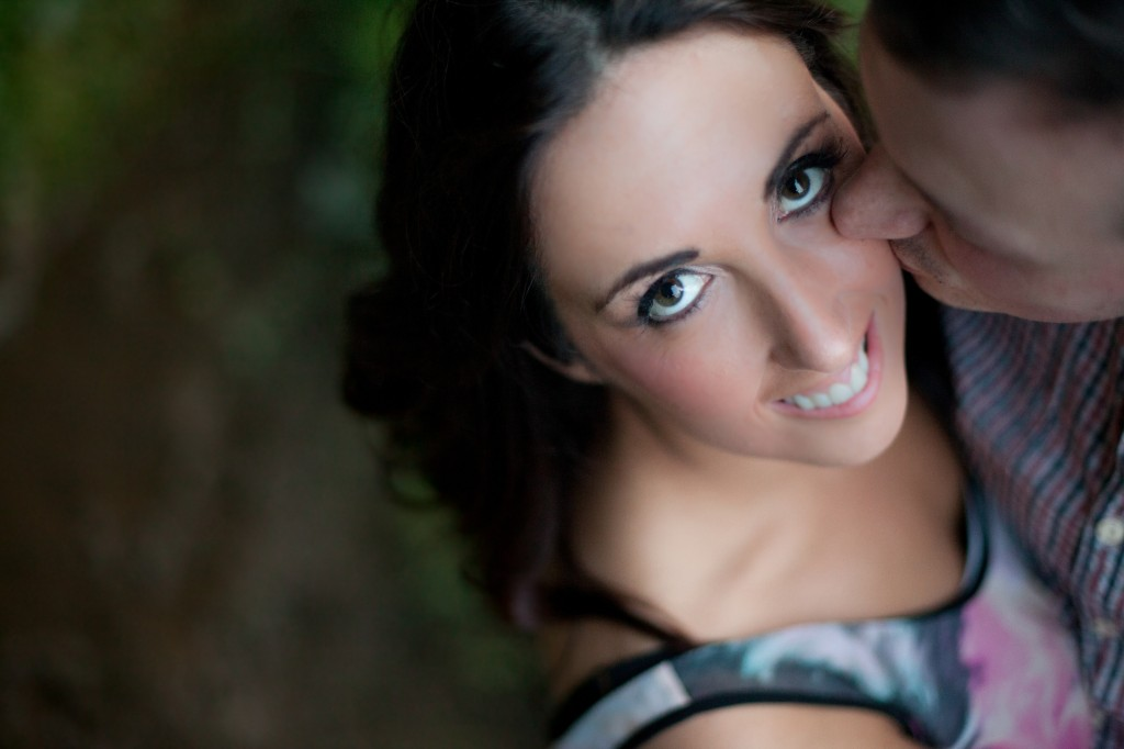 A bride looks up at the camera as her Fiance kisses her on the cheek in Lancaster