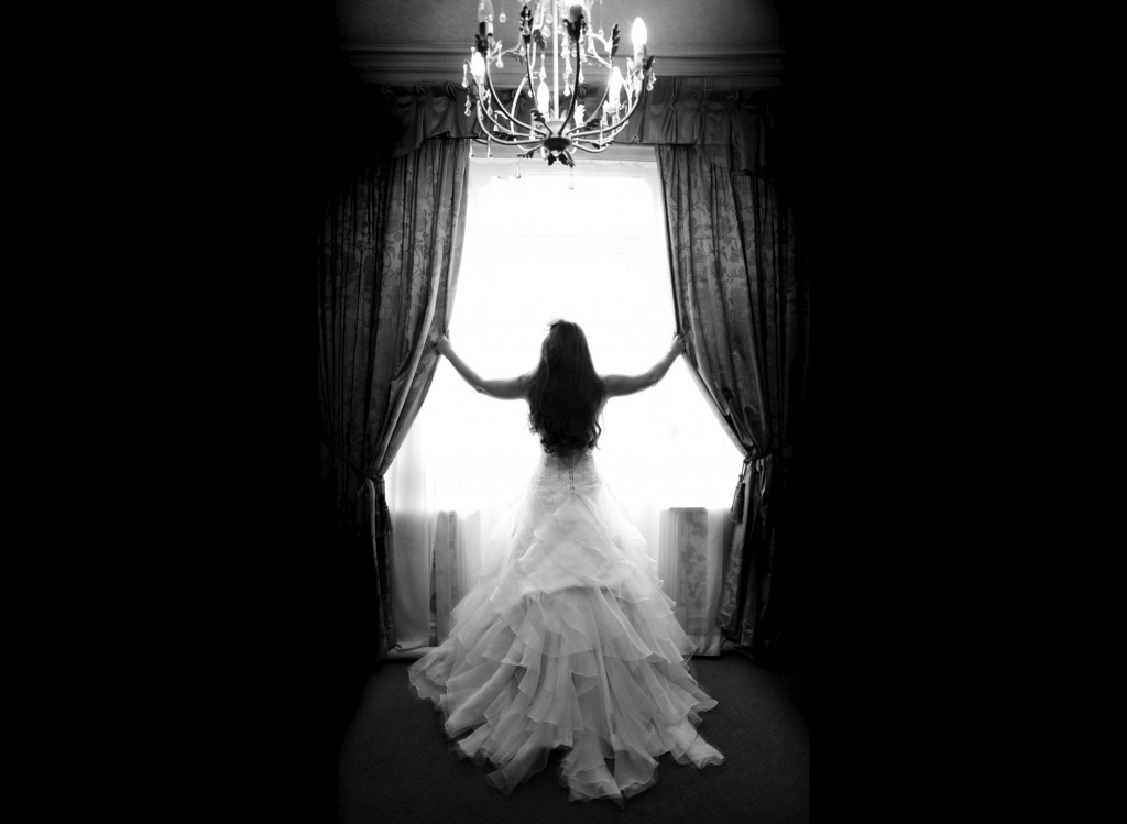 A beautiful Bride stands in the window of Northop Hall, beautiful and creative wedding photography Wales and beyond