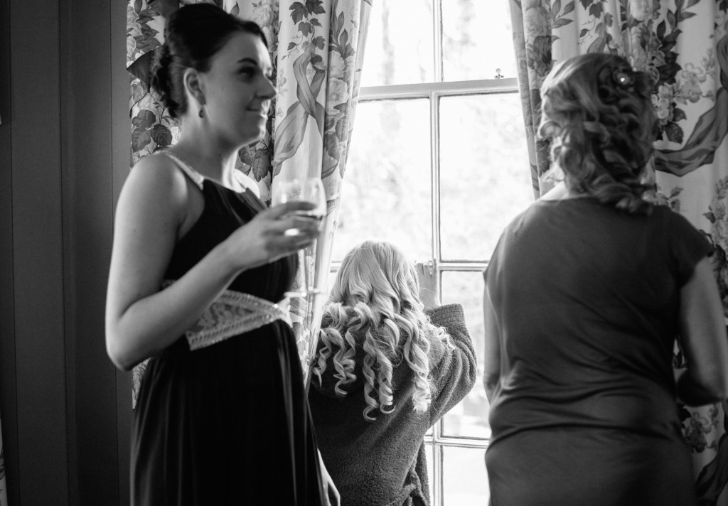 Bridesmaid looks out of window