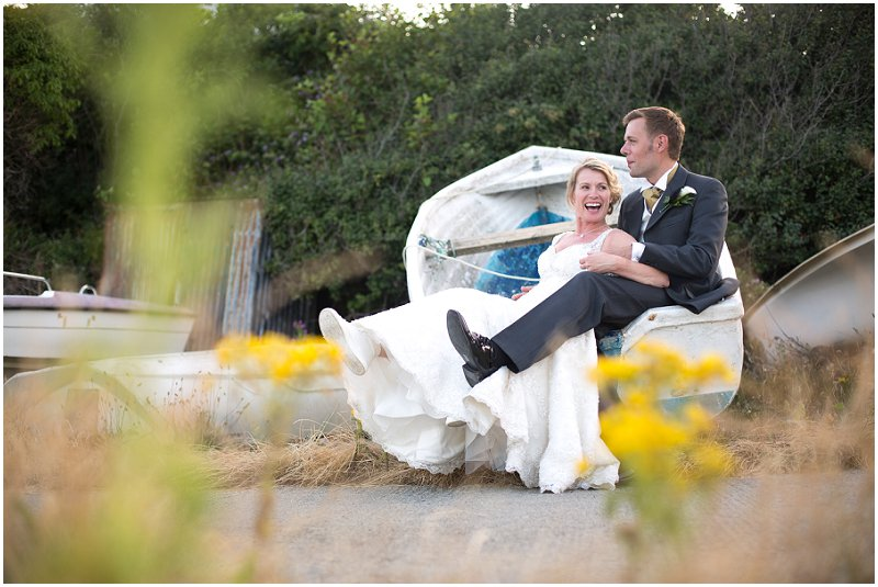 Bride and groom in a boat at Wales wedding