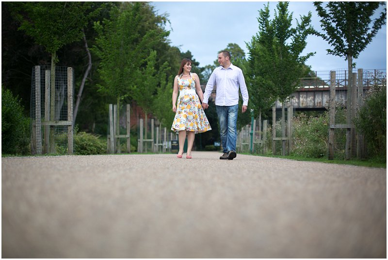 A couple walking during engagement shoot, holding hands