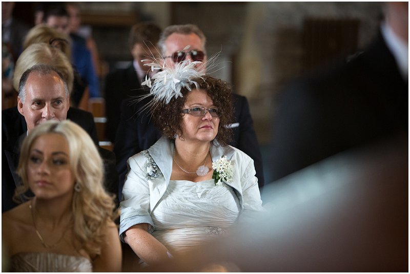 Wedding guest sits in church watching ceremony