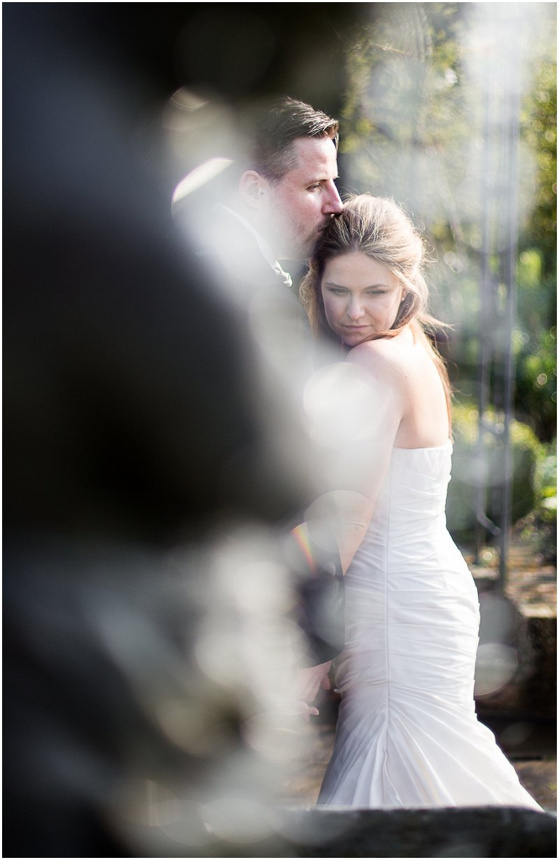 Beautiful couple pose in gardens embracing during wedding portraits