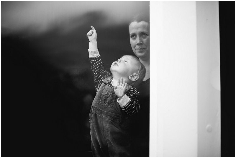 Child looking out window of wedding reception at The Inn on the Lake Photography
