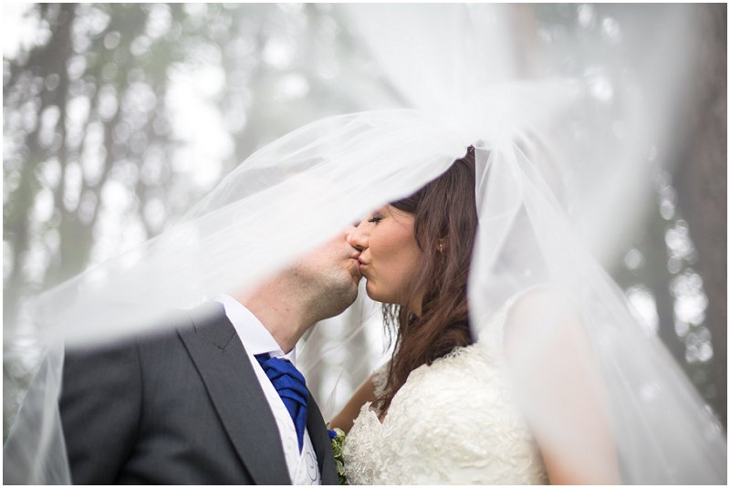 Beautiful bride and groom kiss under veil at Abbey House Hotel Wedding