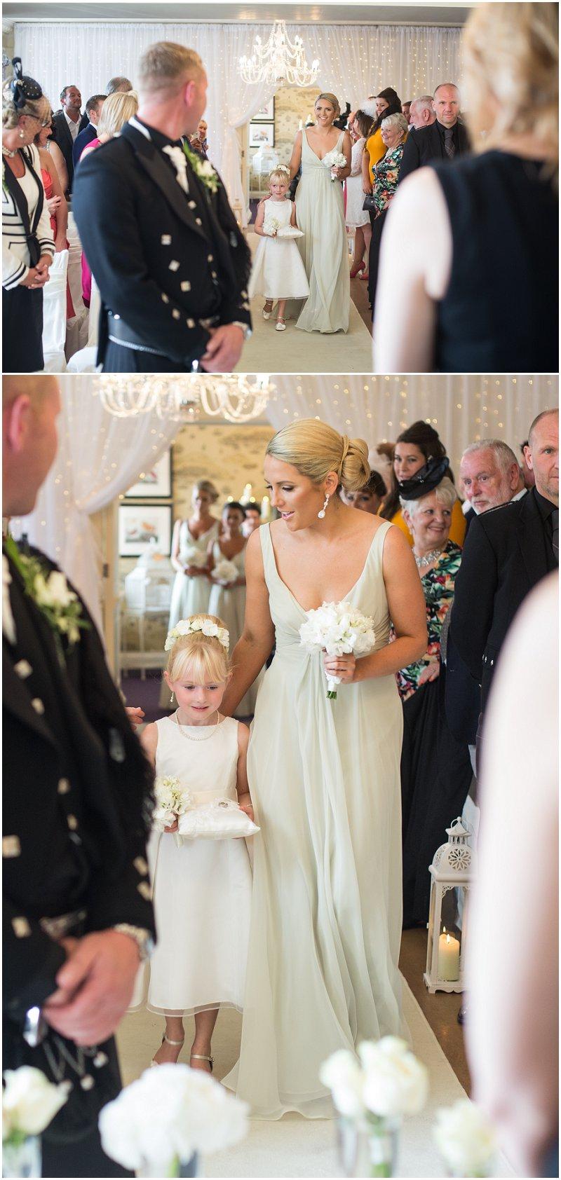 Bridesmaids walking down aisle at Eaves Hall, Lancashire